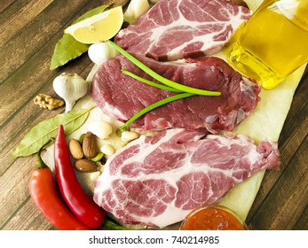raw meat on a wooden board pepper, butter, sauce, nuts, chili, lemon, bay pepper, garlic, organic food, recipe, cooking meat