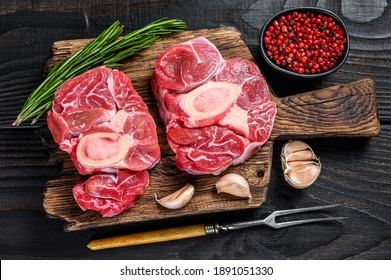 Raw meat osso buco veal shank steak , making italian ossobuco. Black Wooden background. Top view.