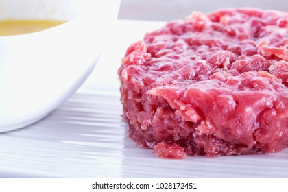 Raw meat over white plate with yellow sauce, horizontal image