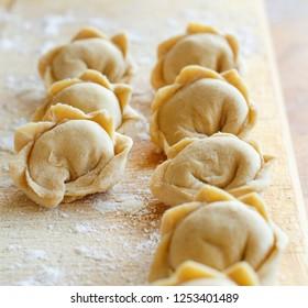 Raw meat pelmeni, ravioli, dumplings top view on a wooden board