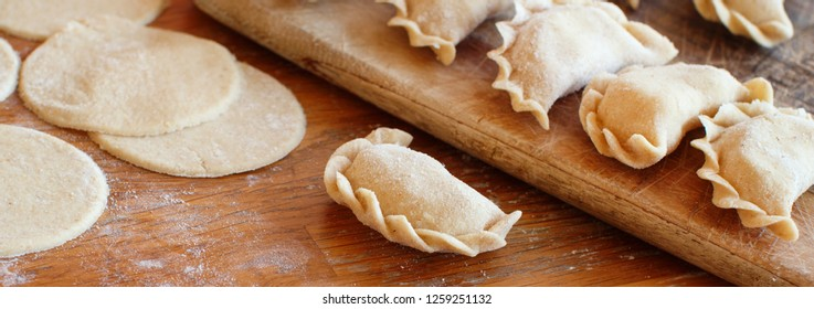 Raw meat pelmeni, ravioli, dumplings on a wooden board