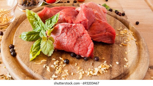 Raw meat in pieces on a wooden cutting board with spices.Ambient light.