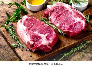 Raw meat Ribeye Steak with seasoning  on dark wooden background. Top view