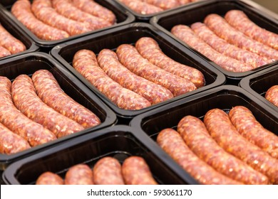 Raw meat sausages in packing box, meat production