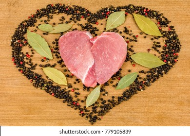 Raw meat in the shape of a heart with pepper and bay leaves on wooden background. A gift on Valentine's Day.
