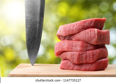 Raw Meat slices and knife on cutting board