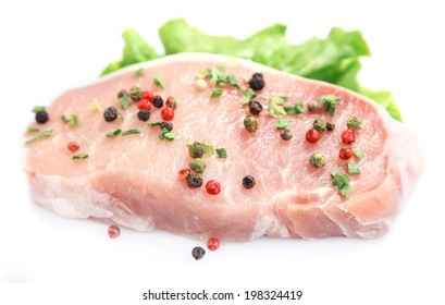 Raw meat steak with leaf lettuce and spices, isolated on white