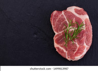 Raw meat,  steak on black background, top view.