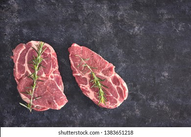 Raw meat steak on dark background. Copy space text concept. Fresh rosemary.