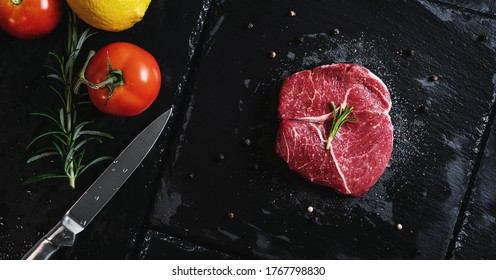 Raw meat steak Tenderloin fillet, with vegetables on black stone plate