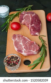 Raw meat steaks, tomatoes, rosemary, salt and pepper on a dark background, vertical frame