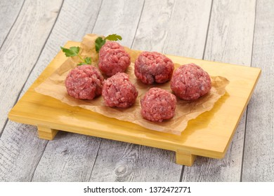 Raw meatball over wooden background ready for cooking