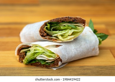 raw meatball wrap made of composition on wooden table divided into two different angles Macro Detail shot buying.