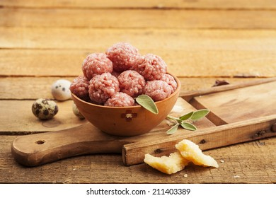 Raw meatballs in bowl with ingredients on wooden background