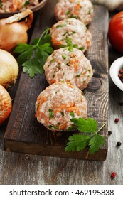 Raw meatballs with herbs on the wooden table