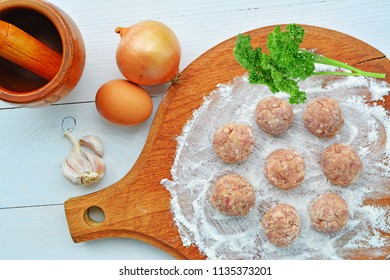 Raw meatballs with ingredients on wooden board ready to be fried.