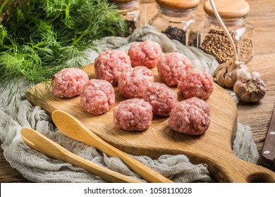 Raw meatballs on the wooden cutting board. Small depth of field.