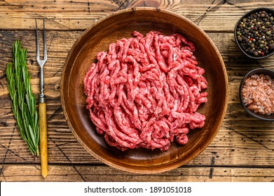 Raw mince lamb, ground mutton meat with herbs on a plate. Wooden background. Top view.