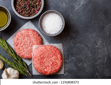 Raw minced homemade grill beef burgers with spices and herbs. Top view and space for text. Pepper, salt and oil on kitchen table background.