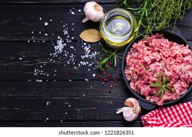 Raw minced meat in bowl  with ingredients for cooking on  black table. Selective focus. View from above with copy space.