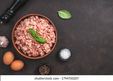 Raw minced meat in bowl on brown table and ingredients. Ground meat with ingredients for cooking on dark background with copy space. Top view or flat lay - Shutterstock ID 1794703207