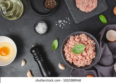 Raw minced meat in bowl on black table and ingredients. Ground meat with ingredients for cooking on dark background with copy space. Top view or flat lay - Shutterstock ID 1810388968