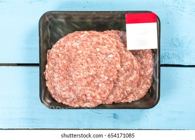 Raw minced meat burgers in the market package with price tag.