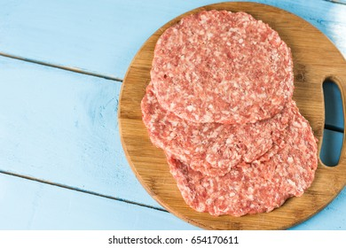 Raw minced meat burgers on the wooden round kitchen board.