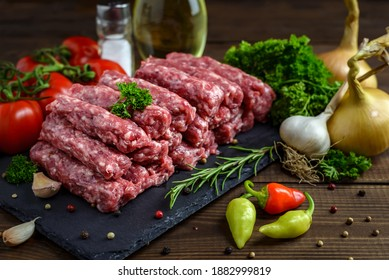 Raw minced meat cevapi ready for barbeque with various fresh vegetables on a wooden table. Selective focus.