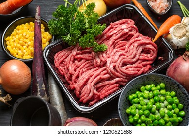 Raw minced meat in container with ingredients for shepherds pie with green peas, yellow corn
