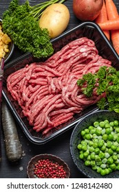 Raw minced meat in container with ingredients for shepherds pie with green peas, yellow corn, carrot, potato, parsley, onion and seasonings, on black background, top view
