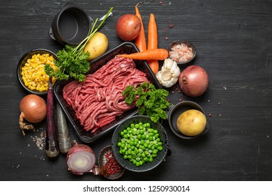 Raw minced meat in container with ingredients for shepherds pie with green peas, yellow corn, carrot, onion and seasonings, on black background, top view