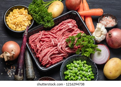 Raw minced meat in container surrounded by ingredients for shepherds pie , green peas, yellow corn, carrot, onion and seasonings, on black background, top view. Horizontal composition