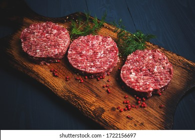 Raw minced meat cutlets with herbs and spices on a wooden Board on a blue wooden background