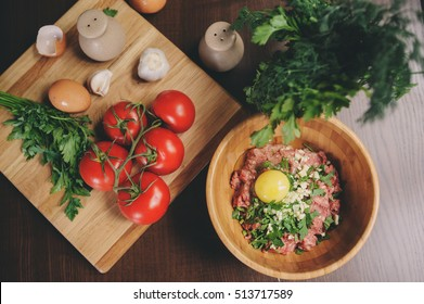 Raw minced meat with egg, herbs and fresh tomatoes on wooden table. Ingredients for cooking meat balls or loaf in rustic kitchen