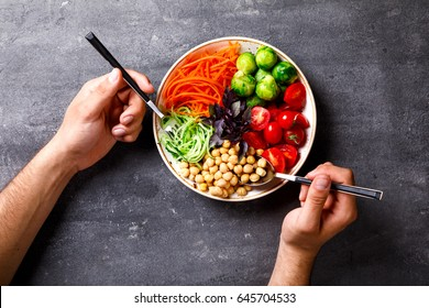 Raw mixed Vegetables and chickpeas.Vegetarian Buddha Bowl in the Men's Hands. Food or Healthy diet Concept.Super Food.Copy space for Text. selective focus.
