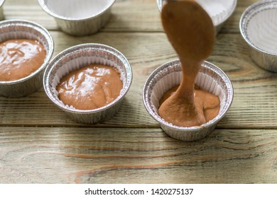 Raw muffin dough in baking dishes on wooden background. Cooking chocolate muffins.