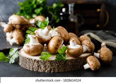Raw mushrooms champignons on black background, cooking fresh champignons