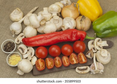 Raw mushrooms on a cutting board. Preparation of Champignons in the kitchen. Spices for food preparation. Vegetables to prepare meals.