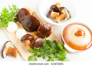 raw mushrooms and other vegetables next to a ceramic pot, close-up food