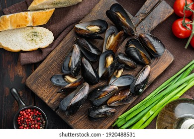 Raw Mussels with herbs lemon and baguette set, on wooden cutting board, on old dark wooden table background, top view flat lay