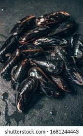 Raw mussels on black stone