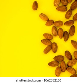 Raw Natural Organic Almonds Nuts Scattered Isolated on Yellow Background Top View Healthy Food for Life Natural Light Selective Focus