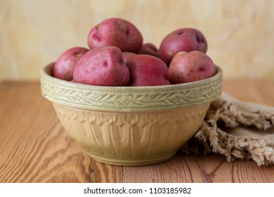 Raw New Red Potatoes in a Vintage Yellow Bowl on a Wooden Table against a Yellow Plaster Wall