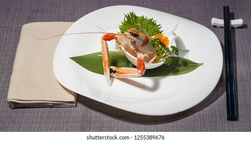 Raw Norway lobster with orange caviar, served with vegetable julienne, green leaves for decoration