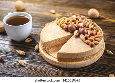 Raw nutty cake decorated with walnut, almond, macadamia and hazelnut on a dark wooden background. Healthy fresh vegan dessert. Gluten free and sugar free product