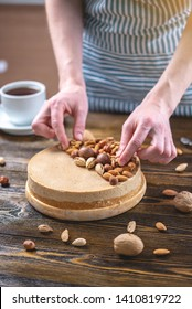 Raw nutty cake decorated with walnut, almond, macadamia and hazelnut on a dark wooden background. Healthy fresh vegan dessert. Gluten free and sugar free food