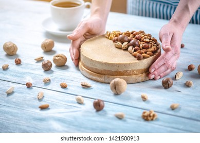 Raw nutty cake decorated with walnut, almond, macadamia and hazelnut on a blue wooden background. Healthy fresh vegan dessert. Gluten free and sugar free food