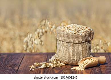 raw oatmeal in bag on table with ripe cereal field on the background. Uncooked porridge oat flakes in burlap sack. Agriculture and harvest concept