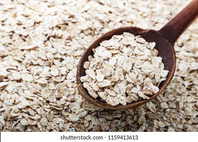 raw oatmeal scattered, on top of a wooden spoon with oatmeal. background